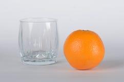 Orange mit leerem Glas Stockfotos