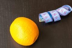 Orange mit messendem Band auf schwarzem Hintergrund, gesundem Lebensstil-, Diät- und Sportkonzept stockfotografie
