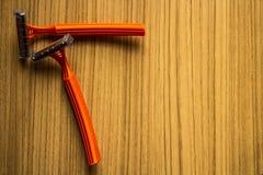 Orange mit zwei Rasierapparaten auf einem hölzernen braunen Boden lizenzfreie stockfotos