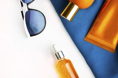 Orange mock up bottles of sun screen and sunglasses on bright contrast blue beach wrap on horizontal empty white background with. Orange mock up bottles of sun royalty free stock photography