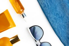 Orange mock up bottles of sun screen and sunglasses, bright contrast blue beach wrap on horizontal empty white background. Holiday stock photography