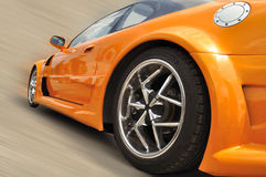 Orange modern car. Orange extreme car with modern wheel rims in motion Royalty Free Stock Photography