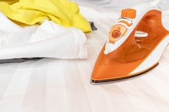 An orange modern electrical iron and a heap of unironed clothes close up - chore concept.  stock image
