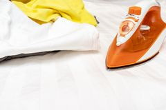 An orange modern electrical iron and a heap of unironed clothes close up with copy space stock image