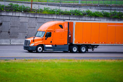 Orange modern semi truck and orange trailer on city road Stock Image
