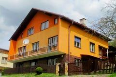 Orange modernt hus för by arkivbilder