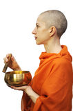 Orange monk. Bald woman in saffron robe with singing bowl, meditating. Isolated on white, clipping path included Stock Images