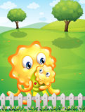 An orange monster carrying her baby monster at the hilltop Royalty Free Stock Photo