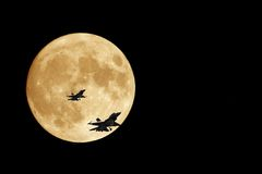 Orange Moon and F16 Jets. F/16 jets silhouetted by a full orange moon Stock Photography