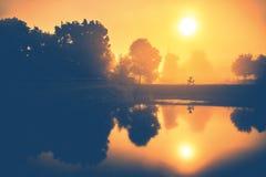 Orange morgon för dimmig soluppgång nära vatten och väderkvarnen royaltyfri bild
