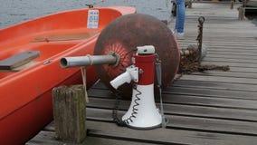 Orange motorbåt, boj och megafon på pir på sjön lager videofilmer