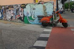 Orange motorcycle stop at lane with graffiti painting on colourful and creative art Royalty Free Stock Photos