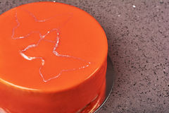 Orange mousse cake covered with glaze. Modern european cake on light marble background Stock Photos