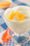 Orange mousse i ett exponeringsglas på rutig servett Arkivbild