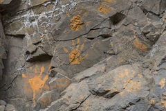 Orange muddy hand prints on stone wall Royalty Free Stock Images