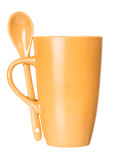 Orange mug with spoon empty blank for coffee or tea Royalty Free Stock Images