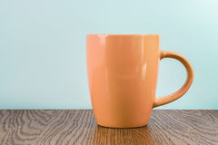 Orange mug standing on a wooden table Royalty Free Stock Photos