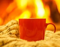 Orange mug for tea or coffee, wool things near cozy fireplace, w Royalty Free Stock Photo