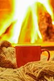 Orange mug for tea or coffee; wool things near cozy fireplace; w Stock Photo