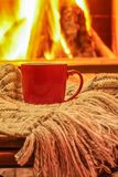 Orange mug for tea or coffee, wool things near cozy fireplace, w Royalty Free Stock Image