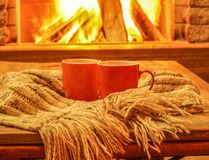 Orange mugs for tea or coffee; wool things near cozy fireplace. Stock Photography