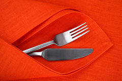 Orange napkin and tablecloth with knife and fork. Royalty Free Stock Photography