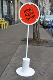 Orange New! New! New! sign in Portland, Oregon. This is an orange sign advertising a new store or product for sale on a sidewalk in downtown Portland, Oregon royalty free stock photos