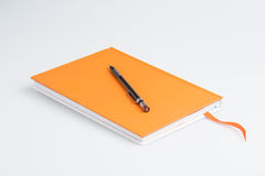 Orange note book and pen Royalty Free Stock Photography