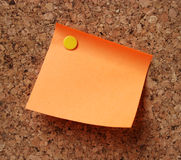 Orange note pad. A detail of an empty orange note pad on cork board Royalty Free Stock Photography