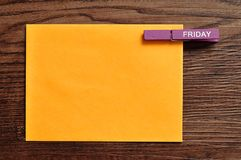 An orange note with a peg with the word friday. On a wooden background Royalty Free Stock Photo