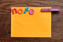 An orange note with the word note and a peg with the word friday. On a wooden background Stock Photo