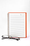 Orange notebook and eyeglasses. Orange notebook (blank paper) and eyeglasses isolated on white background Stock Image