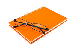 Orange notebook and eyeglasses. Isolated on white background Stock Image