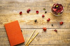 Orange notebook with flower sachets on wooden table Stock Photography