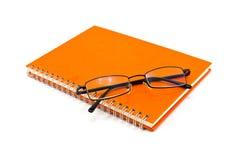 Orange notebook and sunglasses. Orange notebook and eyeglasses isolated on white background royalty free stock photos
