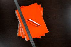 Orange notebooks lying on a dark brown wooden table with an orange and white pens and measure tape Stock Photography