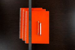 Orange notebooks lying on a dark brown wooden table with an orange and white pens and measure tape Royalty Free Stock Photos