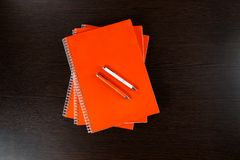 Orange notebooks lying on a dark brown wooden table with an orange and white pens Stock Image