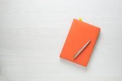 Orange notepad med en penna på vit träbakgrund royaltyfria foton