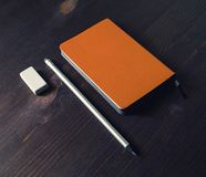 Orange notepad, pencil, eraser. Orange notepad, pencil and eraser on wooden table royalty free stock images