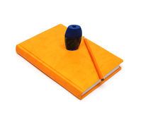 Orange Notizbuch, Bleistift und Bleistiftspitzer Stockfotografie