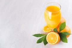 Orange ny citrus fruktsaft med mogna apelsiner och det gröna bladet på det mjuka vita wood brädet, gräns, bästa sikt Arkivbild