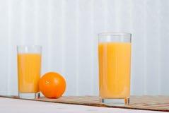 Orange ny fruktsaft bredvid läckra mogna apelsiner på tabellen Royaltyfri Foto