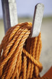 Orange nylon safety rope coiled on metal hook. Orange nylon rope coiled around a metal hook. Focus is on rope at foreground Stock Photo