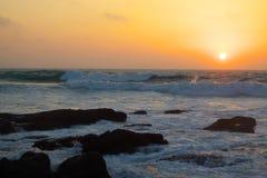 Orange ocean sunset. Orange sunset in stormy ocean with rocks and waves Stock Image