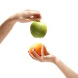 Orange och äpple i händer Royaltyfri Foto