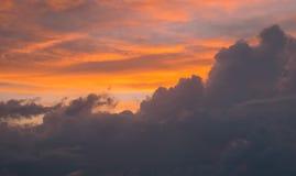 Orange och gråa moln på solnedgången arkivfoto