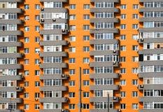 Orange och grått tegelstenhus med många fönster och balkongen Royaltyfri Foto