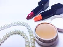 orange och röd fuktighetsbevarande hudkrämläppstift i svart packe Arkivbilder