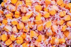 Orange och röd slågen in godis royaltyfri bild